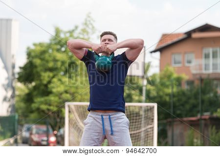 Young Man Doing Kettle Bell Exercise Outdoor