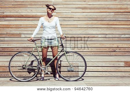 Fashionable beautiful young Pretty girl in shorts and t-shirt stands with bicycle fix gear nex to th
