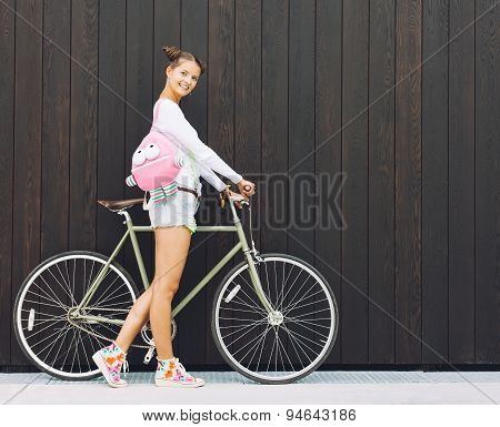 Pretty girl in shorts and t-shirt with a funny pink backpack stands with his bicycle fix gear nex to