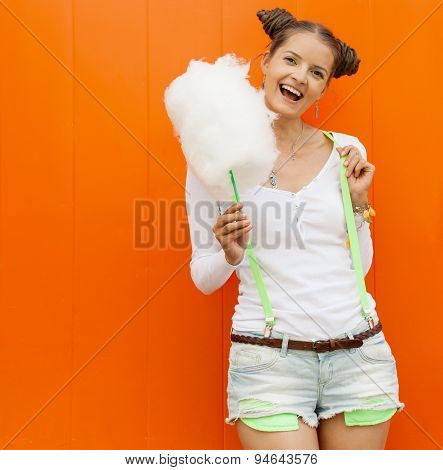 Beautiful fashionable girl  in shorts and t-shirt with cotton candy posing nex to the orange wall