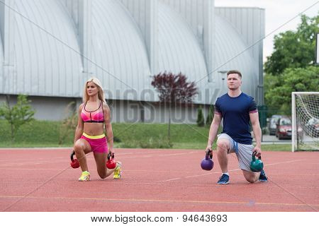 Group Of People Doing Kettle Bell Exercise Outdoor