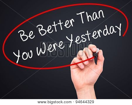 Man Hand writing Be Better Than You Were Yesterday  with black marker on visual screen
