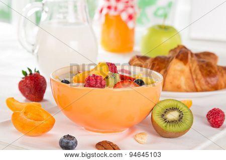 Healthy breakfast with muesli, fruit, tea and berries