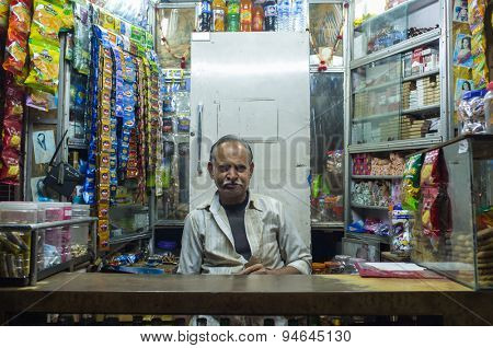 JODHPUR, INDIA - 11 FEBRUARY 2015: Indian vendor sits in shop with gutka hanging in background and other products. Gutka has mild stimulant effect and is consumed by sucking and chewing.
