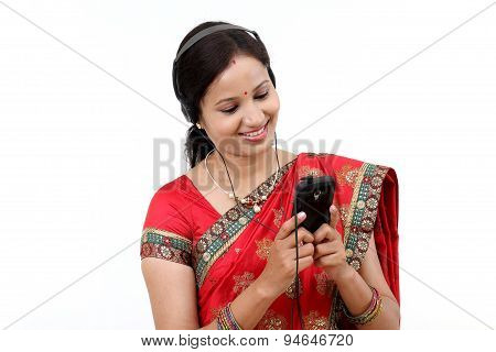 Young Traditional Indian Woman Listening To Music From A Smart Phone