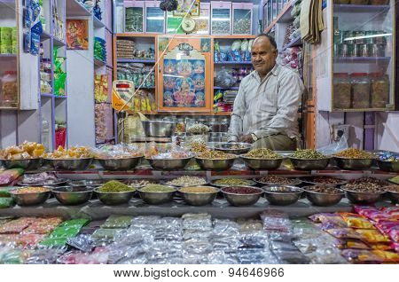 JODHPUR, INDIA - 10 FEBRUARY 2015: Candy shop owner sits while waiting for customers with large variety of mouth-fresheners and sweets on display.