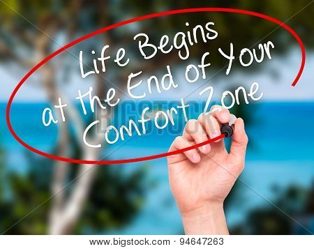 Man Hand writing Life Begins at the End of Your Comfort Zone with black marker on visual screen.