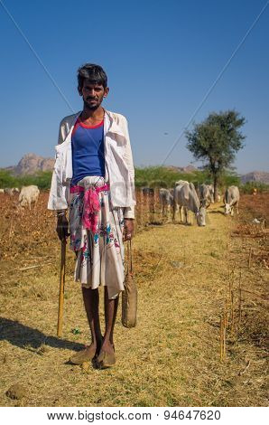 GODWAR REGION, INDIA - 14 FEBRUARY 2015: Young shepherd from Rabari tribe with no turban stands in field with cattle. Holds ax and water bottle. Rabari are an Indian community in the state of Gujarat.