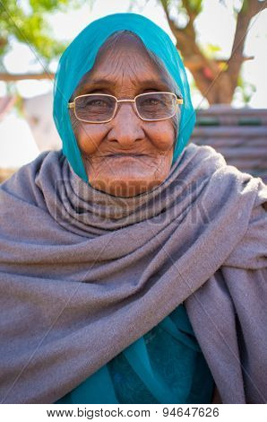 GODWAR REGION, INDIA - 14 FEBRUARY 2015: Elderly Indian woman in glasses with headscarf and blanket around shoulders.