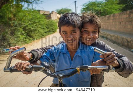 GODWAR REGION, INDIA - 15 FEBRUARY 2015: Two boys on a bicycle in empty village street.