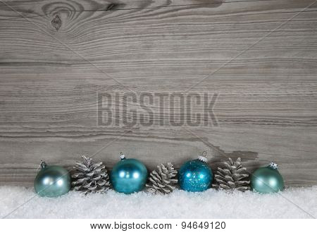 Grey shabby chic christmas background with wood, fir cone and balls in blue color.