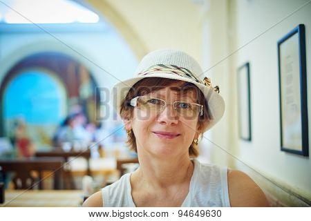 Beautiful woman in hat sitting in coffee