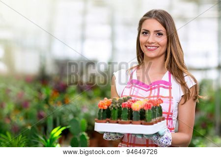 cheerful woman holding a cactus in greenhouse