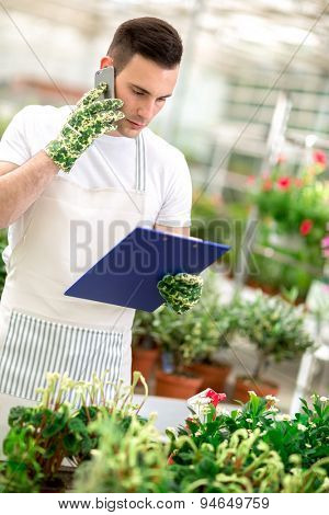 florist In greenhouse taking order over mobile