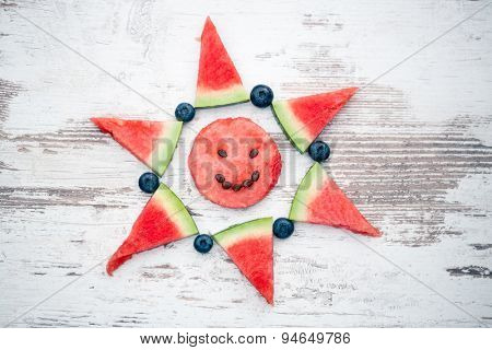 Watermelon and blueberry arranged in funny shape of the sun, top view