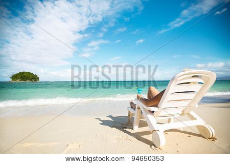 Relaxing and enjoying on summer vacation, woman with cocktail lying in sunbed on beach