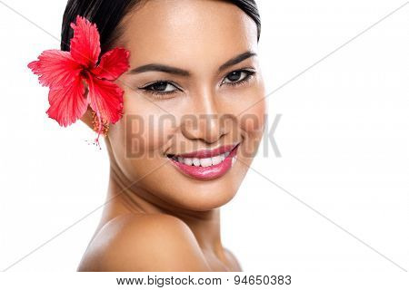 Charming woman with hibiscus flower, smiling ad looking at camera