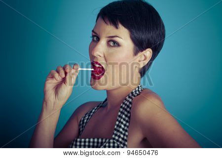 Eat, happy young woman with lollypop  in her mouth on blue background