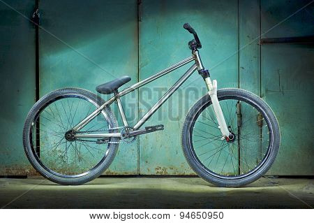 Silver bicycle on a green garage background