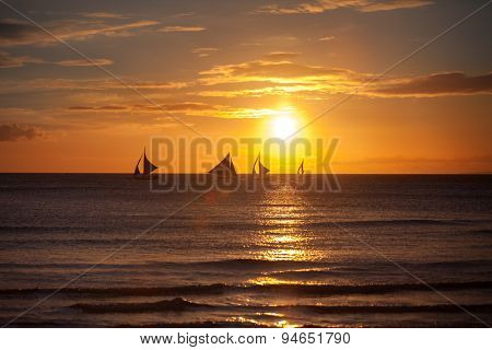Sailboat at sunset on a tropical sea, silhouette photo