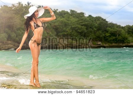 Sunny day on tropical beach, young woman standing in in waves