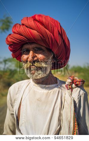 GODWAR REGION, INDIA - 14 FEBRUARY 2015: Elderly Rabari tribesman with big red turban stands on road. Rabari or Rewari are an Indian community in the state of Gujarat.