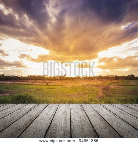Wood Floor And Field Meadow With Beautiful Sunset