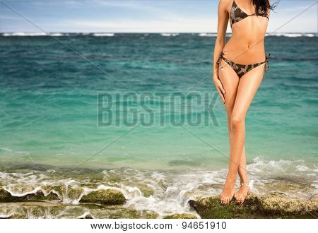 Tanned woman body in bikini on sea background