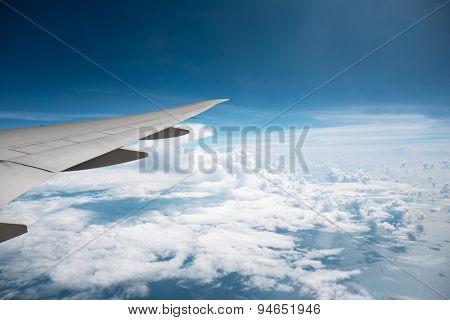 detail wing transport aircraft above the clouds