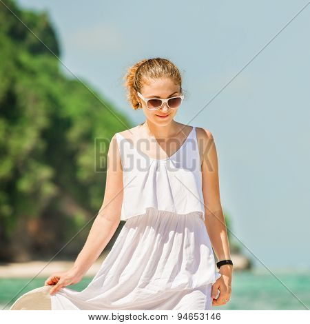 Young woman in long white dress holding hat walks along tropical beach having great summer time on h