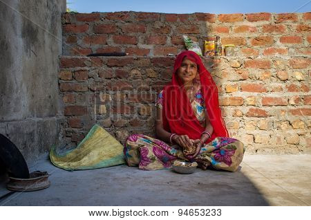 GODWAR REGION, INDIA - 13 FEBRUARY 2015: Indian woman in sari sits and eats chapati for breakfast.