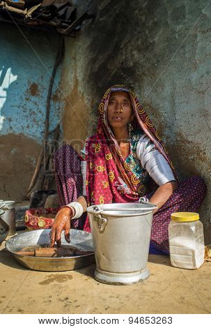 GODWAR REGION, INDIA - 13 FEBRUARY 2015: Rabari tribeswoman in sari decorated with traditional upper-arm bracelets cleans dishes. Rabari or Rewari are an Indian community from Gujarat.