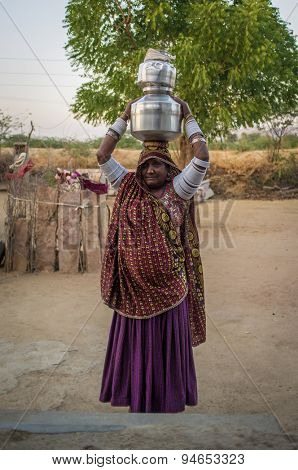 GODWAR REGION, INDIA - 12 FEBRUARY 2015: Tribeswoman decorated in traditional clothes, jewelry and upper arm bracelets holds water pots on head. Rabari or Rewari are an Indian community in Gujarat.