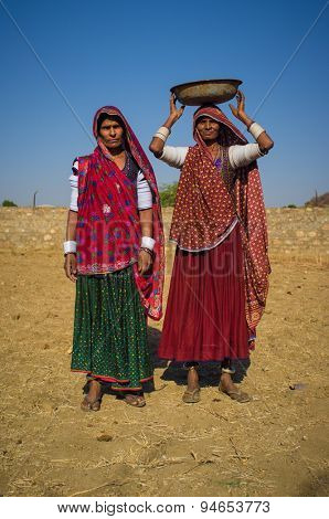GODWAR REGION, INDIA - 14 FEBRUARY 2015: Rabari tribeswomen stand in field wearing sarees and upper-arm bracelets. One balances bucket on head. Rabari are an Indian community in the state of Gujarat.
