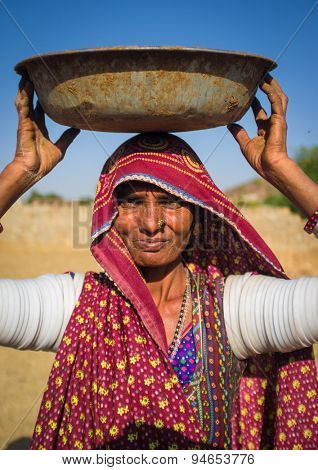 GODWAR REGION, INDIA - 14 FEBRUARY 2015: Rabari tribeswoman stands in field wearing saree and upper-arm bracelets. Balances bucket on head. Rabari are an Indian community in the state of Gujarat.