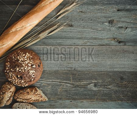 Different types of bread on a wooden background with ears of wheat