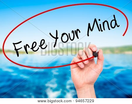 Man Hand writing Free Your Mind with black marker on visual screen.