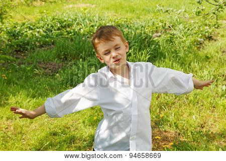 The Little Boy Unties A Tie Against Green Leaves