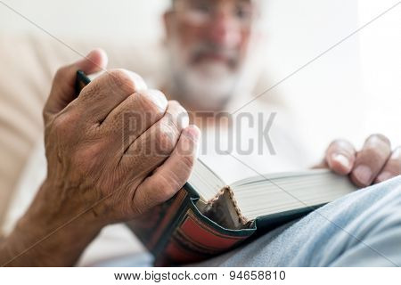 Elderly Arabic man sitting and reading book
