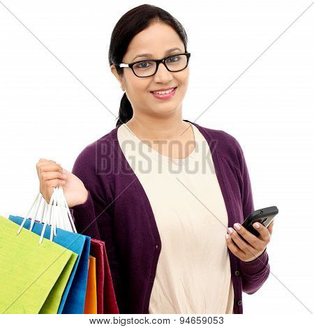 Young Cheerful Woman Holding Shopping Bags And Mobile Phone