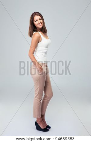 Full length portrait of attractive happy woman standing over gray background