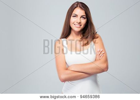 Portrait of a young happy woman standing with arms folded over gray background. Looking at camera