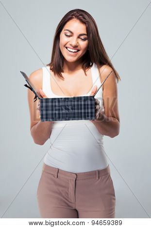 Happy young woman opening gift box over gray background
