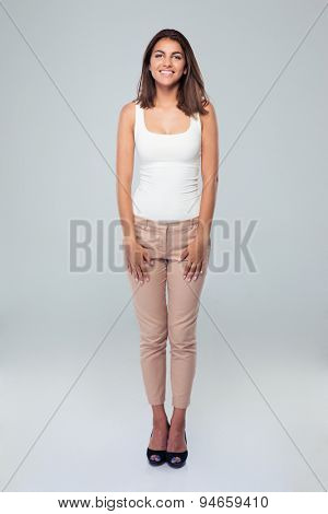 Full length portrait of a  young cheerful woman standing over gray background. Looking at camera