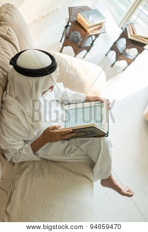 Elderly man sitting and reading Koran
