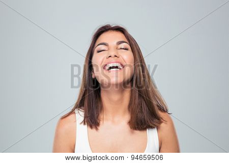 Portrait of a young laughing woman with closed eyes over gray background