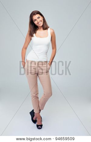 Full length portrait of a young cheerful woman standing over gray background