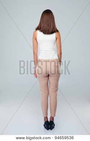 Back view portrait of a casual woman standing over gray background