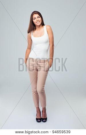 Full length portrait of beautiful smiling woman standing over gray background