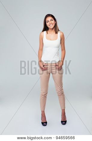 Full length portrait of a casual smiling woman standing over gray background. Looking at camera